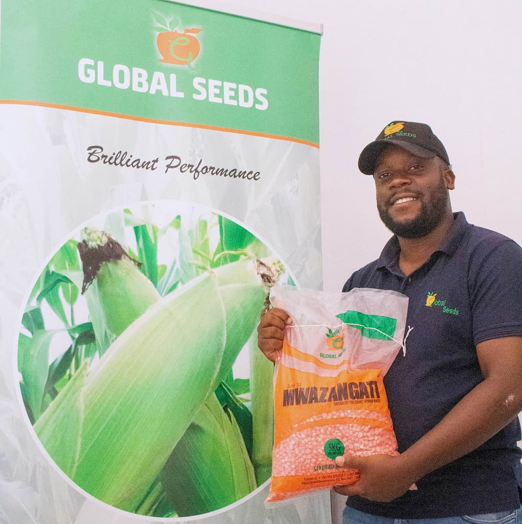 Shane Phiri, Operations Manager at Global Seeds, shows a bag of MH34 seed. (Photo: Emma Orchardson/CIMMYT)