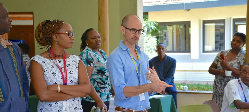 Jordan Chamberlin (center) talks to colleagues during a staff gathering in Nairobi. (Photo. Joshua Masinde/CIMMYT)