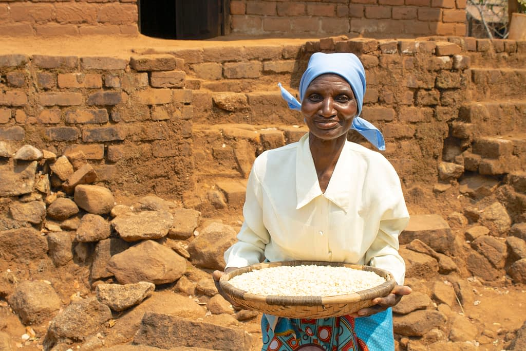 Rose Aufi shows some of her maize grain reserves. (Photo: Shiela Chikulo/CIMMYT)