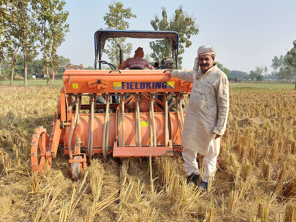 Surender Prasad stands next to his Happy Seeder-mounted tractor in Uttar Pradesh, India. (Photo: Nima Chodon/CIMMYT)