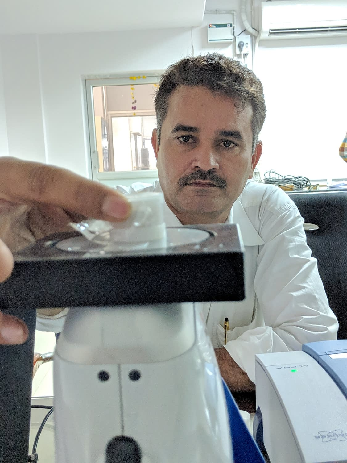 CIMMYT scientist Shishpal Poonia places a soil sample on the Tracer instrument for soil spectroscopy analysis.