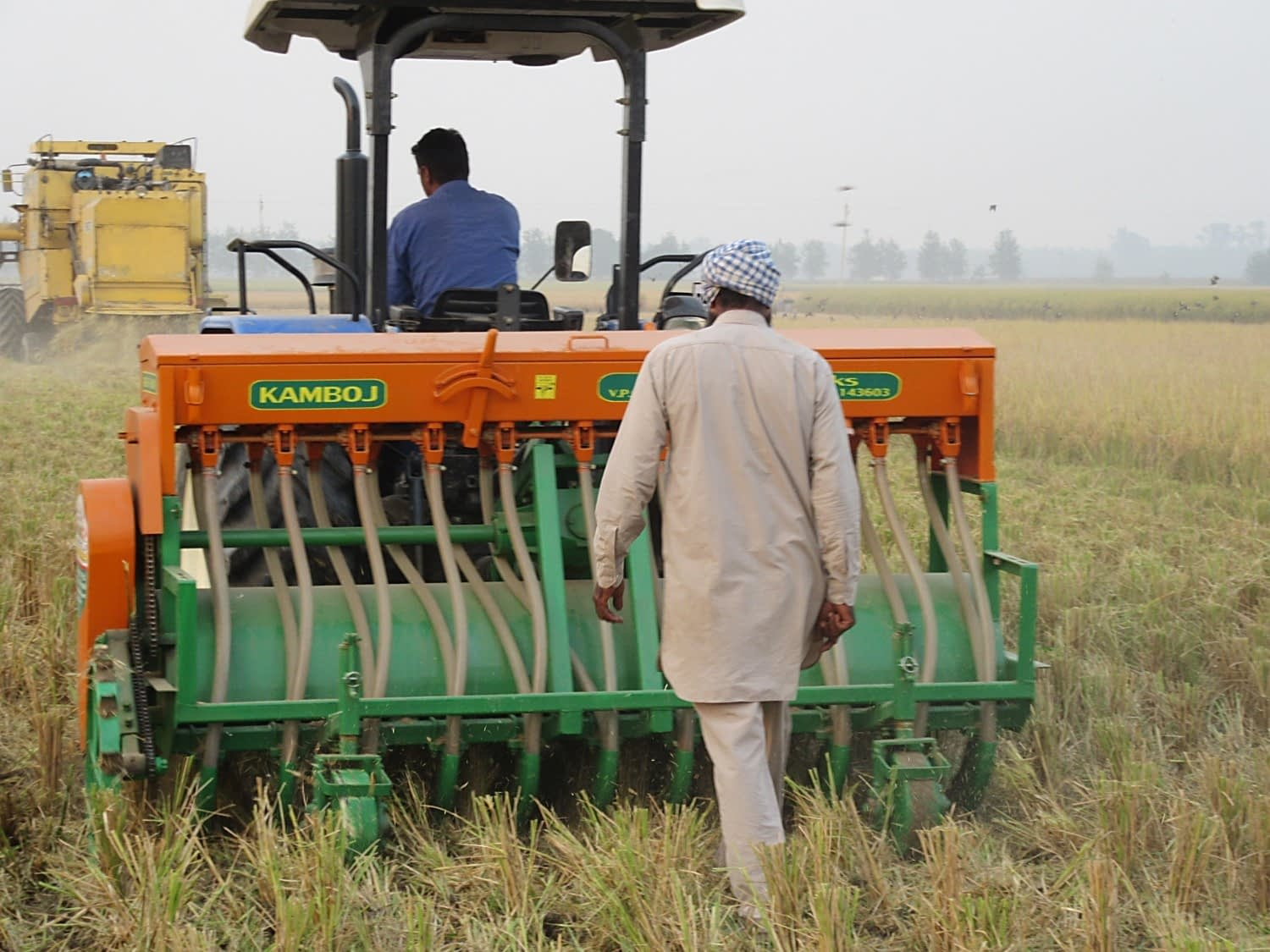 "Direct sowing of wheat seed into a recently-harvested rice field using the ""Happy Seeder"" implement, a cost-effective and eco-friendly alternative to burning rice straw, in northern India. (Photo: BISA/Love Kumar Singh)"