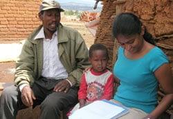 Nilupa Gunaratna, the paper's main author, helps a farmer and his daughter fill out a QPM survey in Karatu, Tanzania.