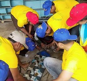 Participants working on a machine part.