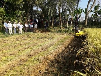 The deputy administrator of USAID and his attaché observe a rice and wheat crop harvester piloted by an entrepreneurial farmer turned businessman. Photo: Md. Aktarul Islam/CIMMYT-Bangladesh