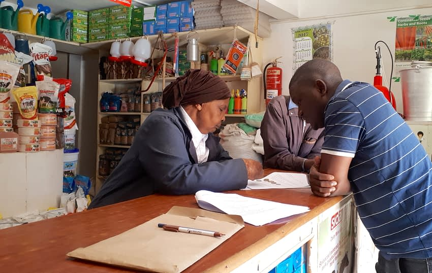 The 70-year-old owner of a farm input shop in Kikuyu town, Kiambu County, answers the questions of CIMMYT researchers. (Photo: Jerome Bossuet/CIMMYT)