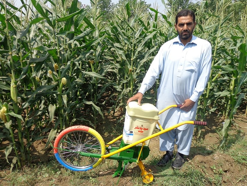 Maize farmer Raham Dil stands for a portrait with his push row planter. (Photo: Kashif Syed/CIMMYT)