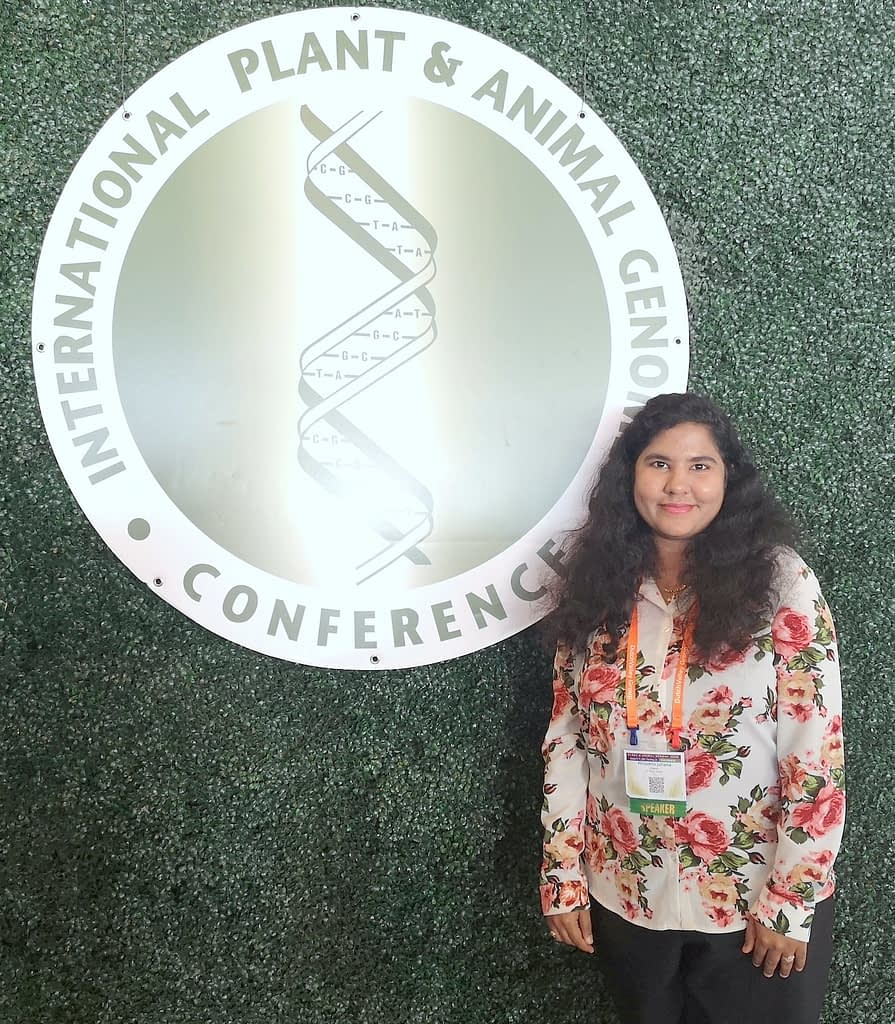 Philomin Juliana stands next to the logo of the PAG conference. (Photo: CIMMYT)